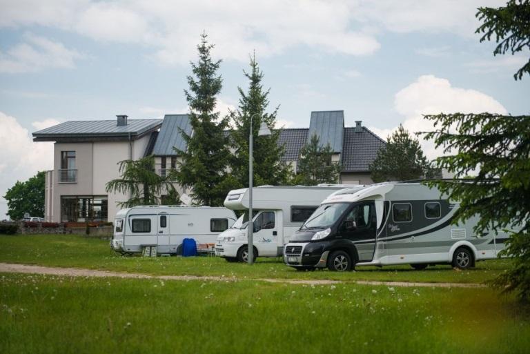 Kemping Wagabunda w Mikołajkach. Na zdjęciu zaparkowane dwa kampery i przyczepa na polu biwakowym obok recepcji ośrodka.