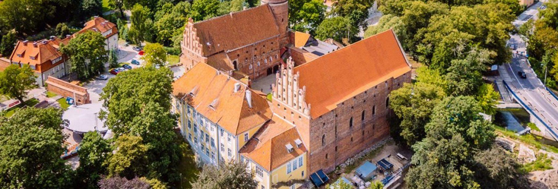 Zamek w Olsztynie z lotu ptaka. Zamek zlokalizowany w centrum obok Starego Miasta w Olsztynie otoczony drzewami.