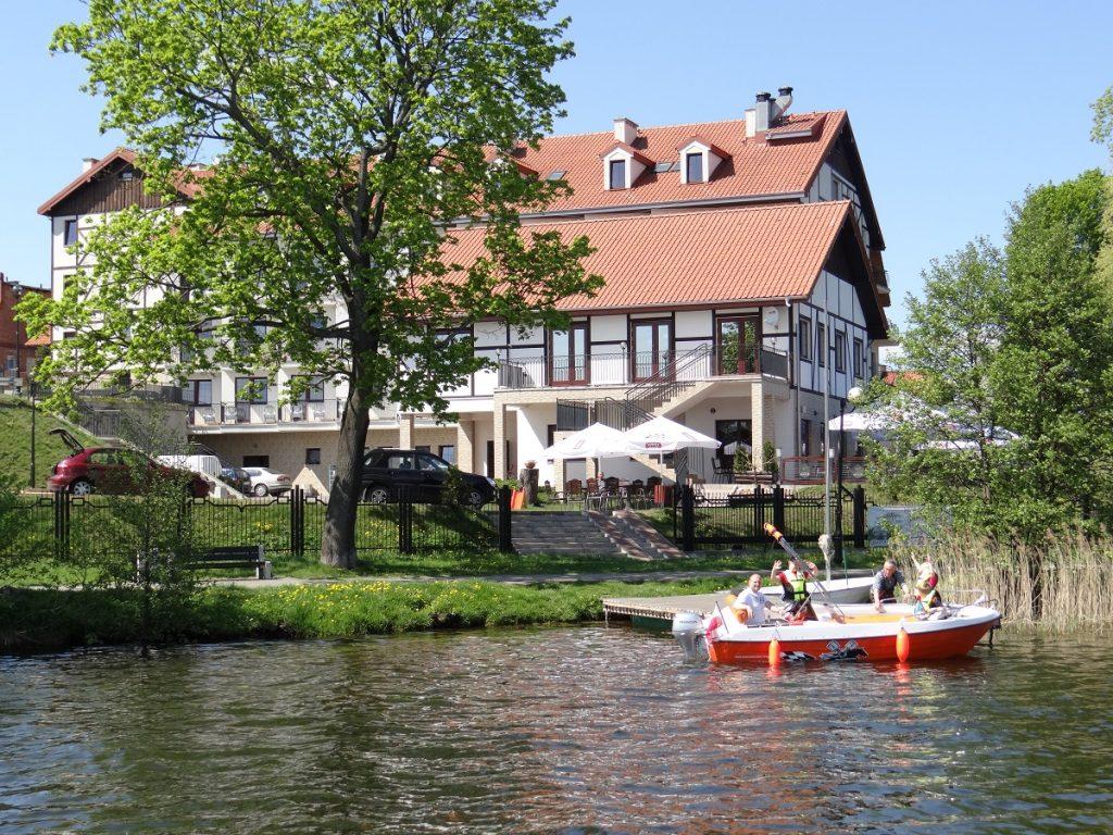 Panorama hotelu Anek w Mrągowie. Na zdjęciu budynek hotelu od strony jeziora Czos a przy pomoście widzimy wodowaną łódkę z turystami.