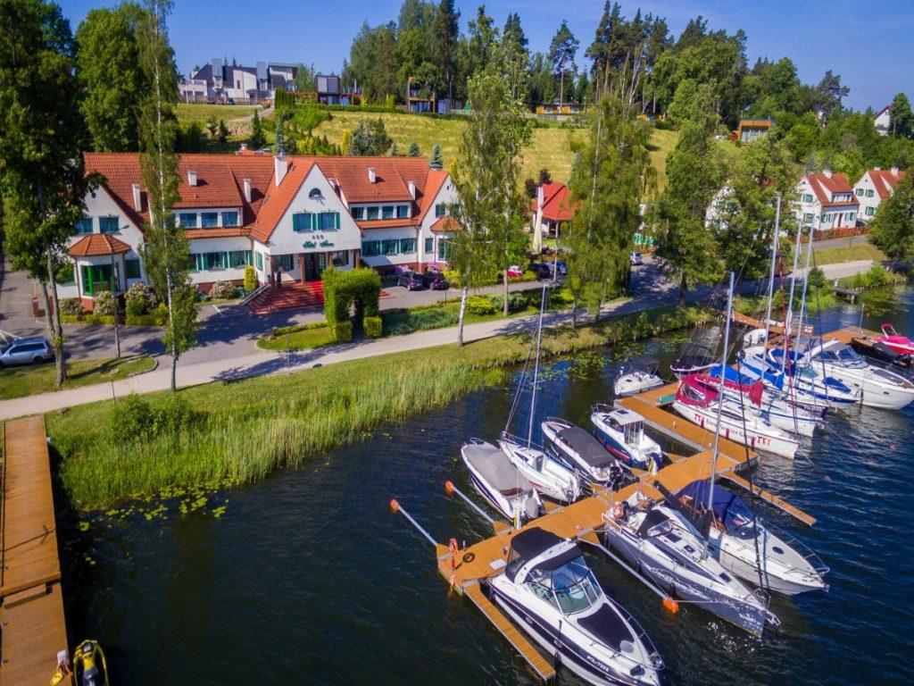 Panorama hotelu Amax w Mikołajkach z lotu ptaka. Widok hotelu, budynku głównego od strony jeziora. Na jeziorze przy pomoście hotelu zacumowane jachty i łódki.