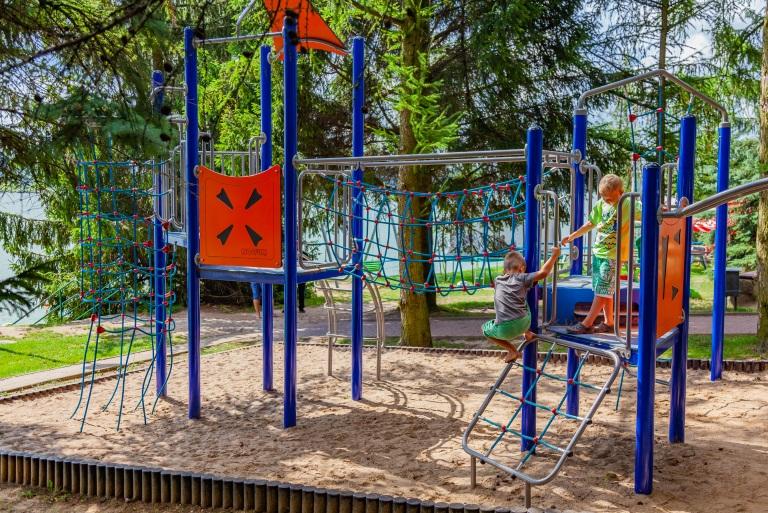 Hotel Robert's Port plac zabaw obok hotelu. Na placu zabaw bawią się dzieci.
