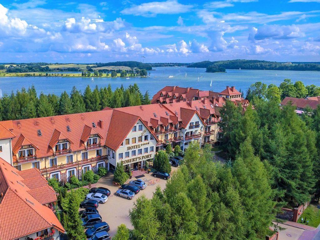 Widok z lotu ptaka panoramy hotelu Robert's Port w Starych Sadach. Za hotelem widzimy panoramę jeziora po którym pływają żaglówki.