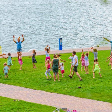 Hotel Robert's Port w Starych Sadach. Na zdjęciu widzimy bawiących się dzieci z rodzicami i prowadzącymi zajęcia animatorami. Zajęcia prowadzone są nad brzegiem jeziora obok hotelu Robert's.