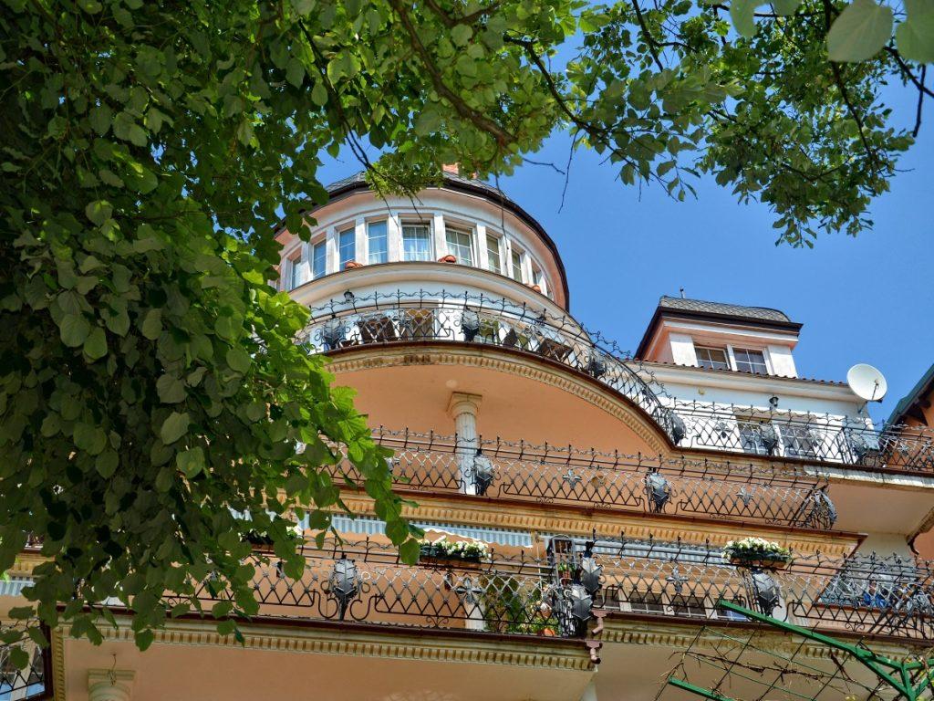Zdjęcie palisady Hotelu Solar Palace w Mrągowie. Na zdjęciu widzimy balkony na różnych piątrach hotelu, a obok po prawej stronie konary drzewa które zasłaniają znaczną część zdjęcia hotelu.