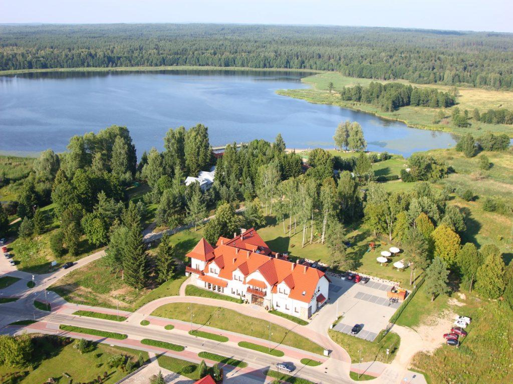 Panorama hotelu Ventus w Gołdapi z lotu ptaka. Na zdjęciu główny budynek hotelu, za hotelem drzewa a za nimi widok jeziora otoczonego lasem.