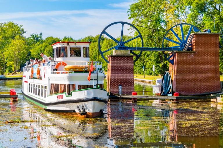 Statek Żeglugi Ostródzko-Elbląskiej podczas rejsu i przeprawiania się  pomiędzy jedną ze śluz kanału. Na statku turyści obserwujący przepłynięcie statku obok śluzy i drugim brzegiem kanału.