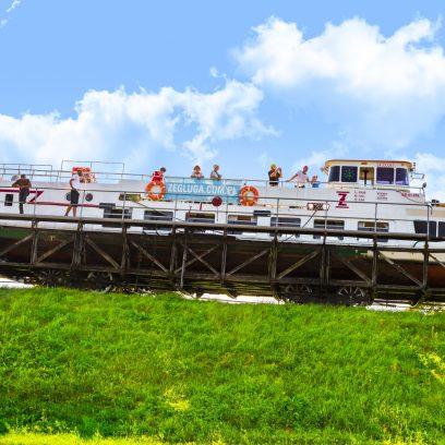 Na zdjęciu statek Żeglugi Ostródzko-Elbląskiej na wózku,  przemieszczający się po torowisku, które znajduje się na trawiastym wzniesieniu. Na statku znajdują się turyści obserwujący trasę.
