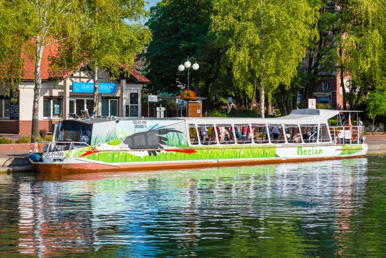 Statek Żeglugi Ostródzko-Elbląskiej wypełniony turystami, przycumowany w porcie na miejskiej przystani.