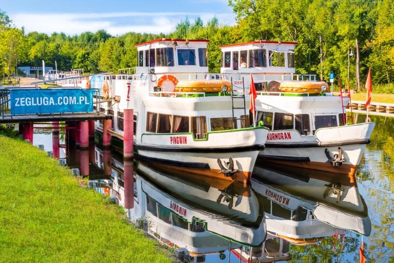 Dwa statki Żeglugi Ostródzko-Elbląskiej, przycumowane na kanale  do pomostu, oczekujące na turystów.