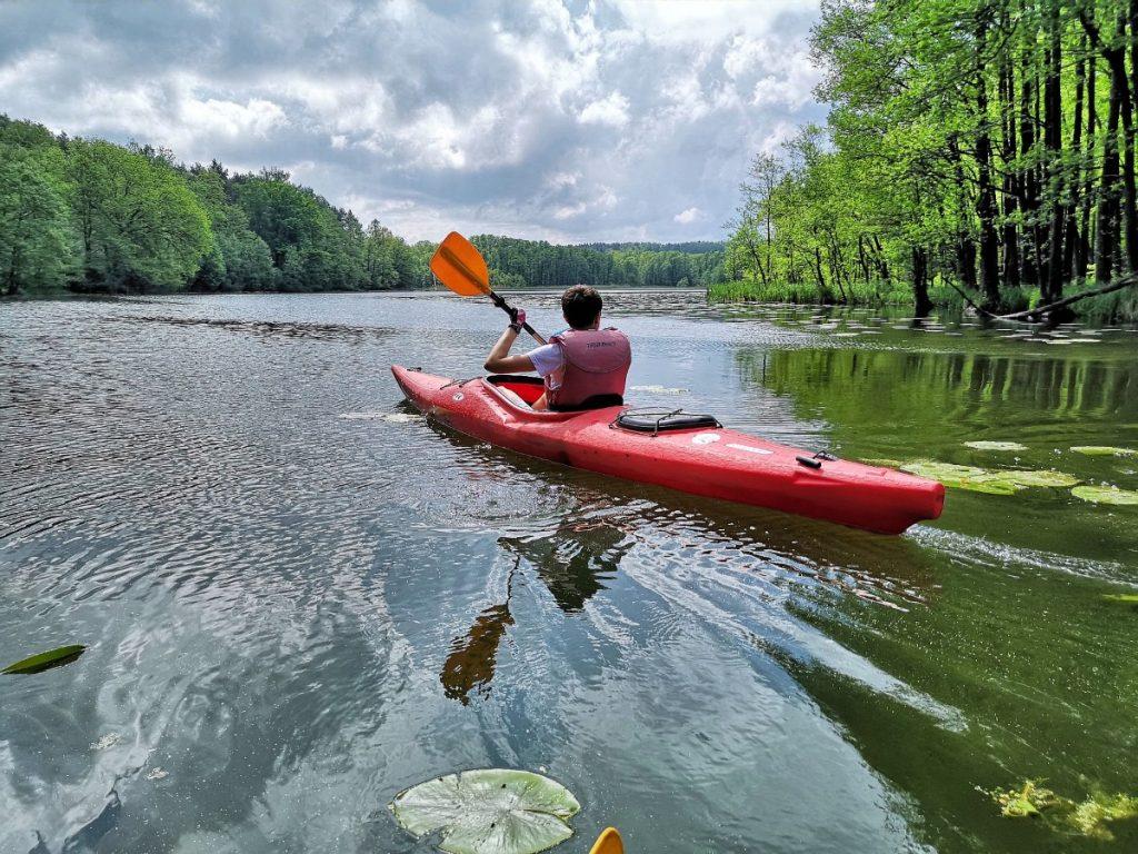 Samotny kajakarz płynący rzeką Krutynią w jednoosobowym czerwonym kajaku.