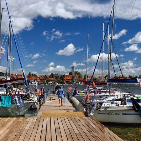 Przystań żeglarska w Mikołajkach. Na zdjęciu kładka na przystani do której po prawej i lewej stronie są zacumowane jachty i łodzie żeglarskie.