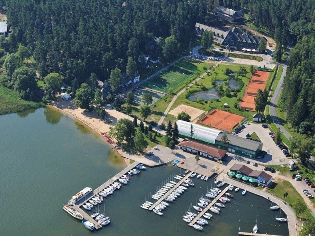 Panorama Ośrodka AZS Wilkasy z lotu ptaka. Na zdjęciu widzimy otoczony lasem budynek główny ośrodka, boiska do piłki nożnej i tenisa ziemnego oraz przystań jachtową z restauracją i tawerną oraz pomosty do których są zacumowane jachty i łódki.