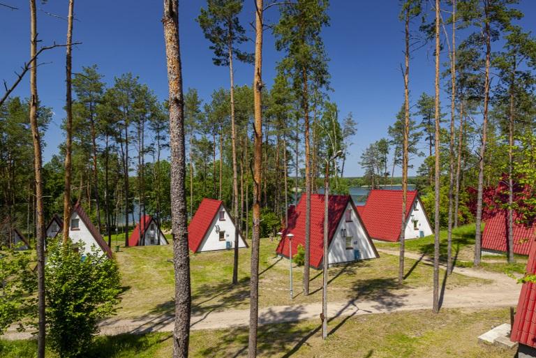 Ośrodek Wypoczynkowy Kalwa w Pasymiu. Na zdjęciu domki letniskowe typu Brda, rozmieszczone pomiędzy drzewami ośrodka. Domków na zdjęciu jest osiem.