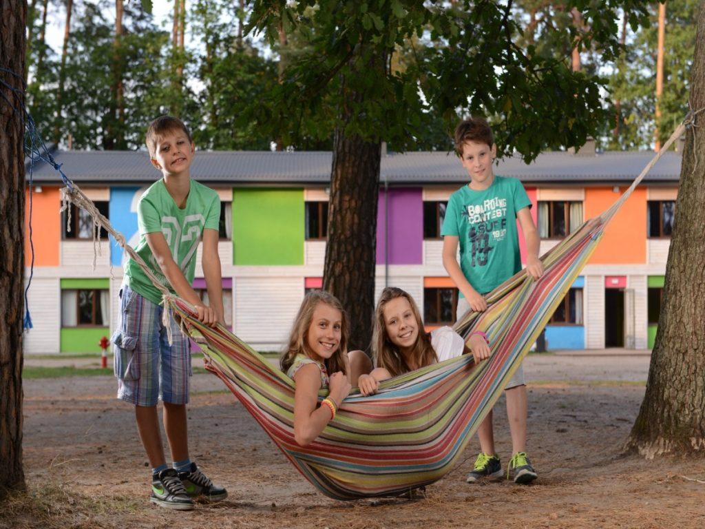 Zdjęcie czwórki dzieci bawiących się hamakiem w Ośrodku Wypoczynkowym Kulka. W hamaku siedzą dwie dziewczyny-nastolatki, a po obu stronach hamaka, stoją dwaj chłopcy trzymający hamak.
