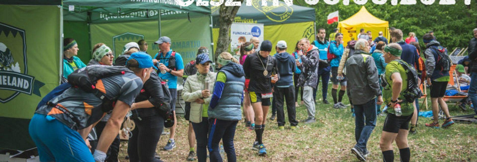 Plakat zapraszający na II Jesienny Ultramaraton Warmiński WARNELAND ŁAŃSK 2020. Na zdjęciu stojący uczestnicy biegu przy namiotach organizatorów, podczas spożywania posiłków.