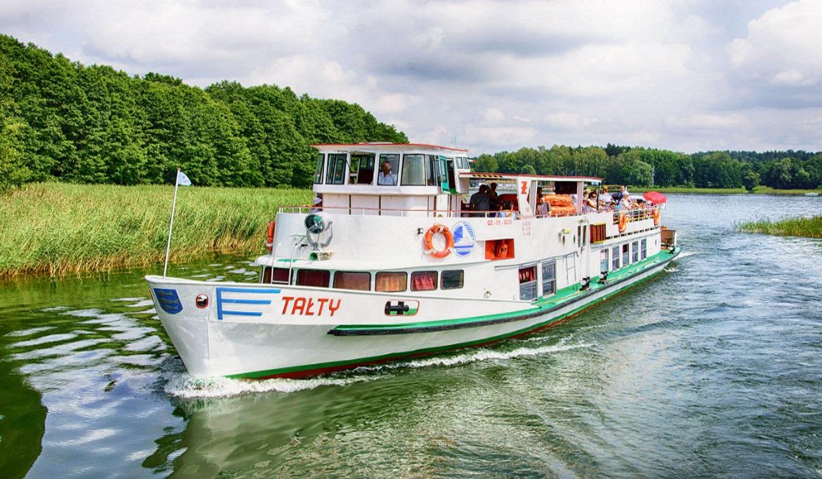 """Na zdjęciu statek wycieczkowy Żeglugi Mazurskiej """"Tałty"""" podczas rejsu, przepływający przez przesmyk."""