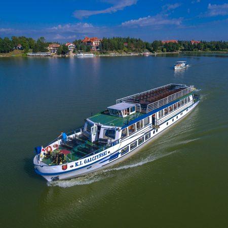 """Na zdjęciu panorama statku wycieczkowego """"Gałczyński"""" pływającego po jeziorze Tałty."""