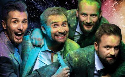 Zdjęcie przedstawia artystów z Kabaretu Skeczów Męczących ubranych w garnitury, zadowolonych, a wokół nich rozsypane są kolorowe proszki.