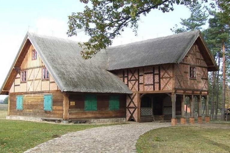 Zdjęcie chaty mazurskiej w Muzeum Budownictwa Ludowego w Olsztynku. Chata zbudowana z gankiem.