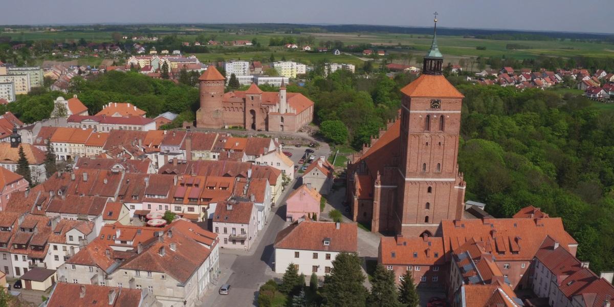 Panorama miasta Reszel z lotu ptaka. Na zdjęciu zamek w Reszlu, kościół oraz centrum miasta z zabytkowymi domami pokrytymi czerwoną dachówką.