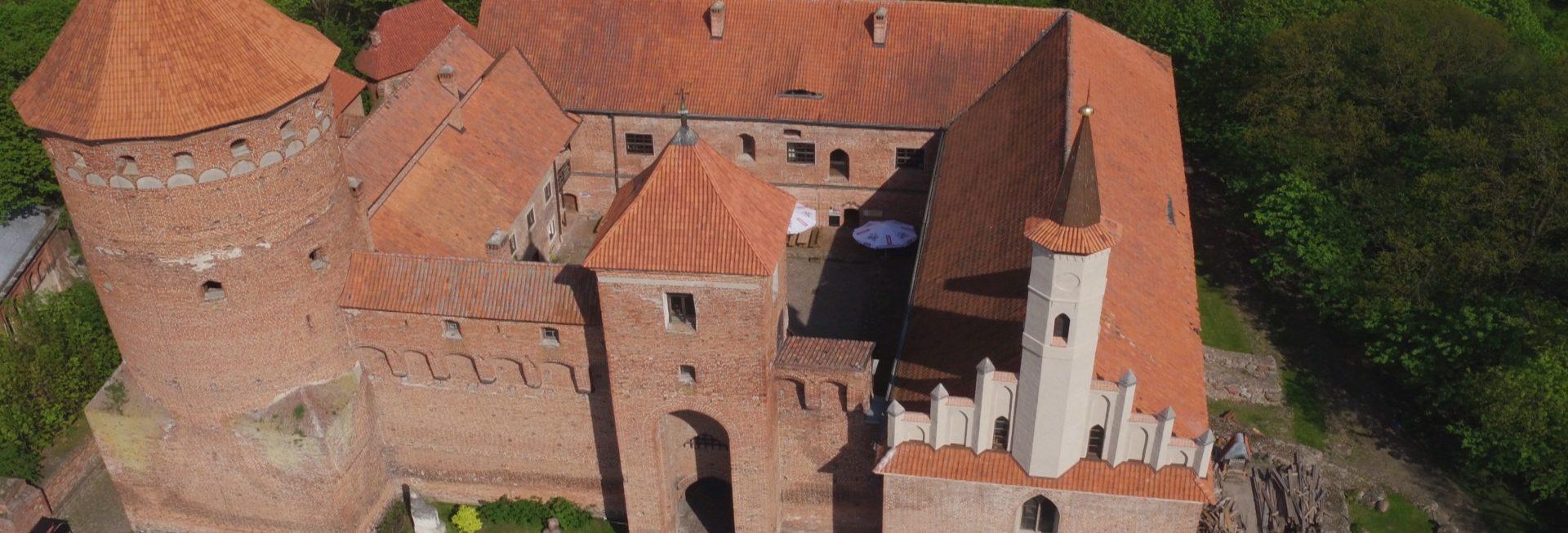 Zamek w Reszlu z lotu ptaka. Na zdjęciu panorama budynku Zamku Reszel zbudowanego z czerwonej cegły. Wokół zamku drzewa.