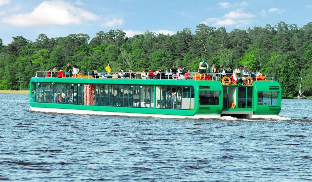 """Na zdjęciu katamaran pasażerski  wypływający z portu """"U Faryja"""" w Rucianem-Nida, podczas rejsu z turystami na pokładzie."""