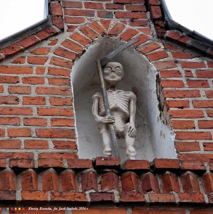 Zdjęcie przedstawia rzeźbę kostuchy jako kościotrupa z kosą, która stoi we wnęce nad braną kościoła w Kiwitach.