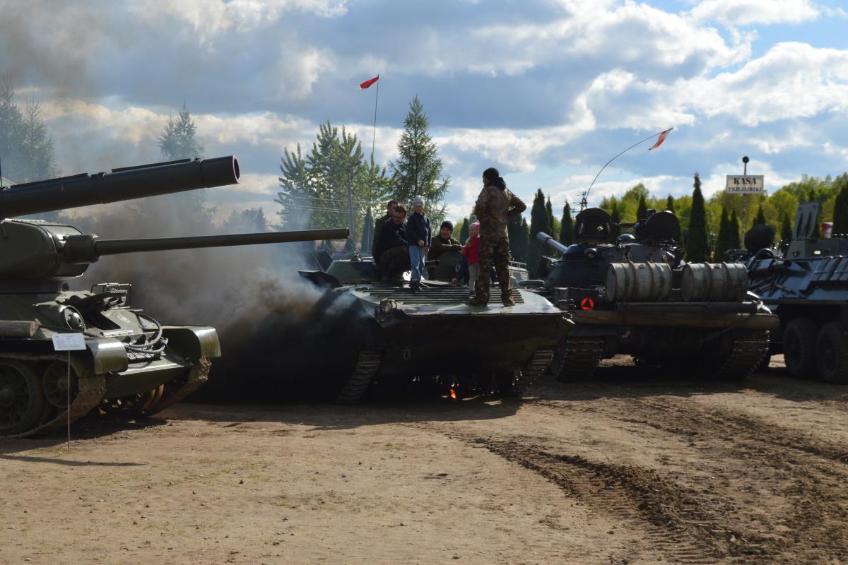 Na zdjęciu czołgi z Mrągowskiego Muzeum Sprzętu Wojskowego poustawiane w rzędzie. Na czołgach turyści z dziećmi zwiedzający sprzęt wojskowy.