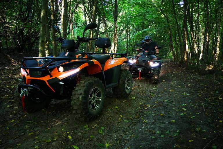Na zdjęciu dwa quady podczas wyprawy terenowej na leśnej ścieżce. Na jednym z quadów z wypożyczalni w Mrągowie dwoje uczestników wyprawy.