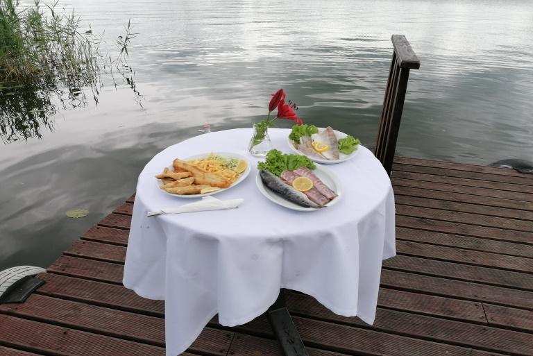 Na zdjęciu nakryty stół ustawiony na pomoście nad jeziorem Czos. Na stole podane są trzy dania z ryby.