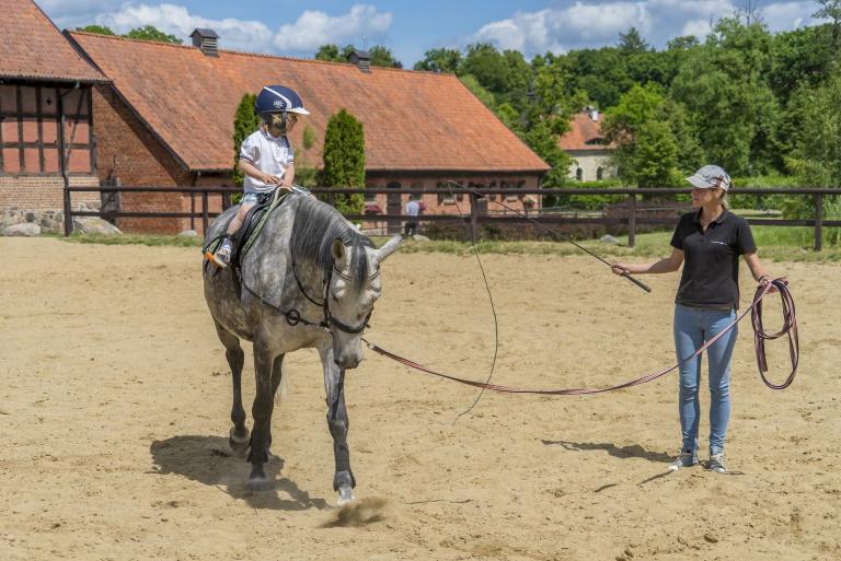 Zdjęcie przedstawiające dziecko siedzące na koniu, a obok konia instruktorkę trzymającą konia na uprzęży w ogrodzonym parkanie Pałacu w Galinach.