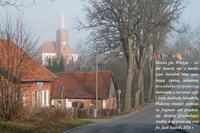 Panorama wsi Nowica od strony drogi. Na pierwszym planie zdjęcia  widzimy dwa budynki z czerwonej cegły a w dali zabytkowy kościół.