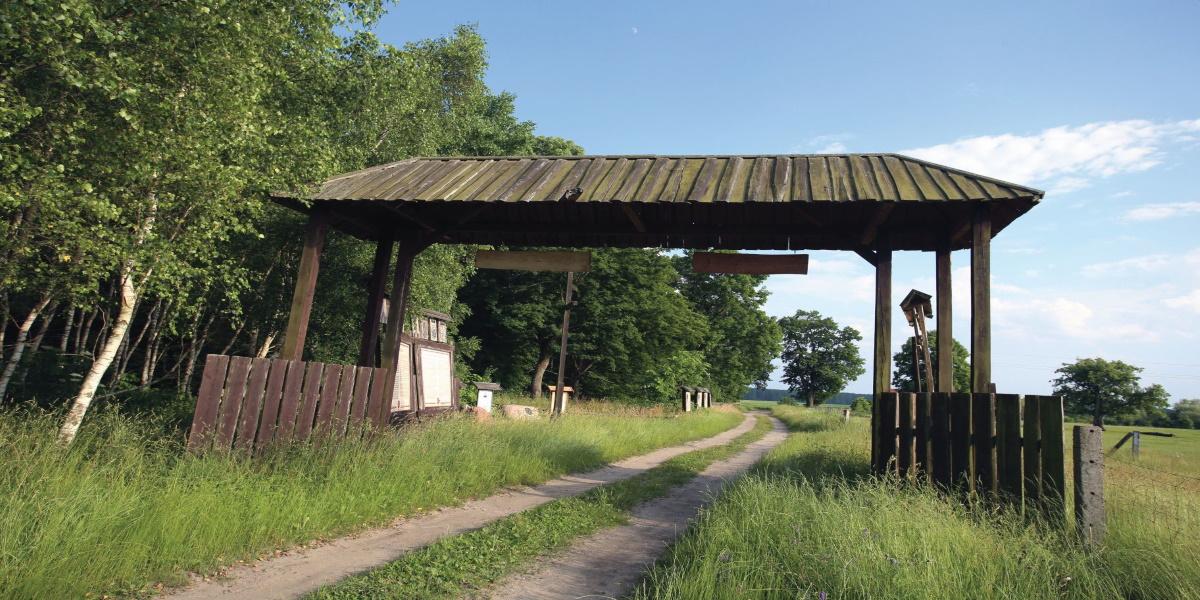 """Na zdjęciu brama z drewnianym dachem w miejscowości Bałdy, symbolizująca dawne """"Wrota Warmii"""". Brama zbudowana jest na polnej drodze."""