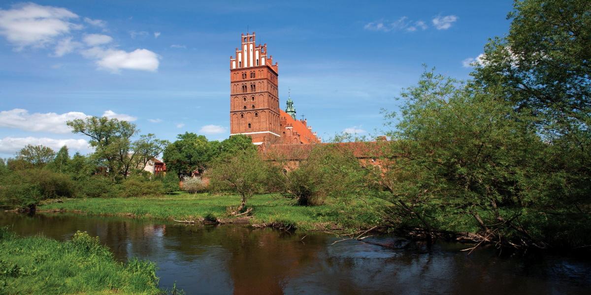 Zdjęcie Kolegiaty Bazyliki Zbawiciela w Dobrym Mieście od strony rzeki. Na zdjęciu widzimy na pierwszym planie wieżę Bazyliki.