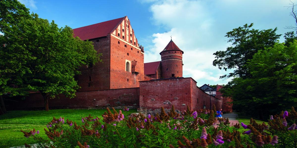 Zdjęcie Olsztyńskiego Zamku Kapituły Warmińskiej od strony parku miejskiego. Na zdjęciu okalający mur oraz wieża zamku.