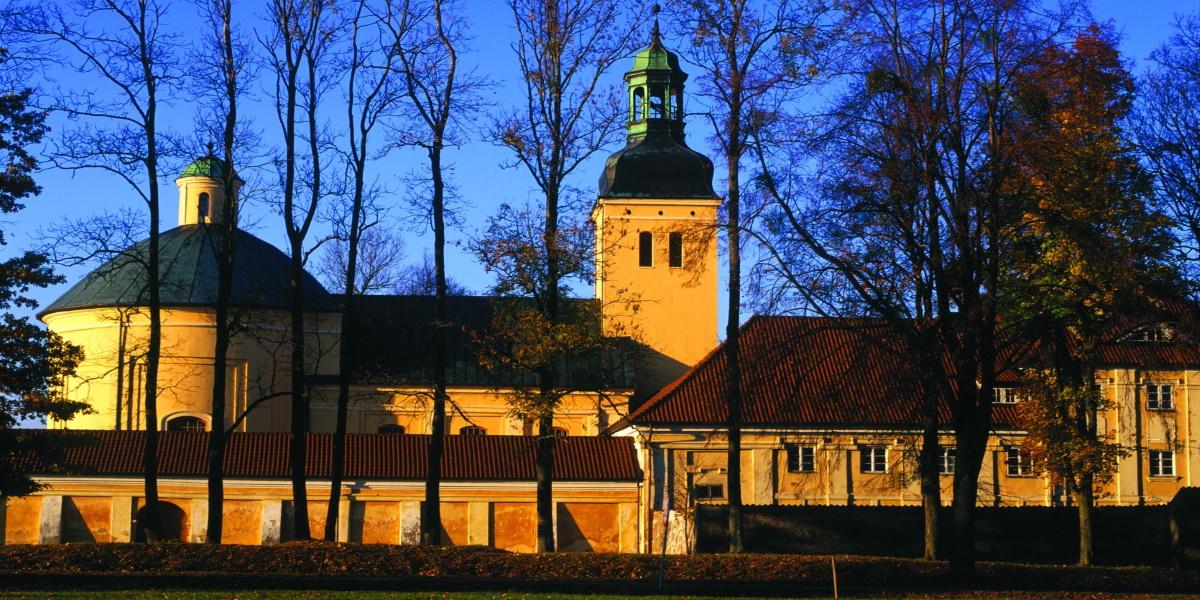 Zdjęcie Kościoła Matki Bożej w Stoczku. Zdjęcie przedstawia kompleks budynków od strony parku.