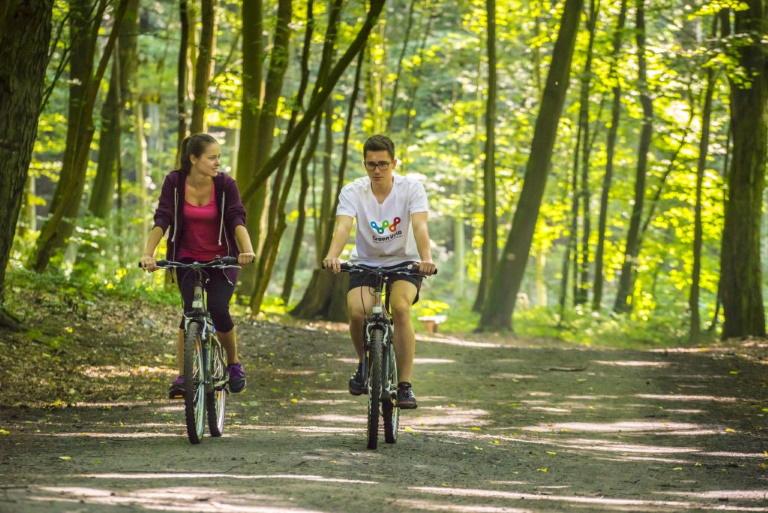 Zdjęcie przedstawia parę rozmawiających ze sobą rowerzystów jadących szeroką leśną ścieżką rowerową.