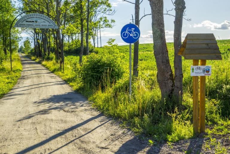 Zdjęcie przedstawia ścieżkę rowerową na trasie Lidzbark Warmiński - Orneta, porośniętej dookoła soczystą zielenią w postaci drzew i łąki.