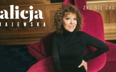 """Plakat zapraszający do Olsztyna na koncert Alicji Majewskiej """"Żyć się chce"""" - Olsztyn 2021. Na zdjęciu piosenkarka siedząca na czerwonym fotelu."""
