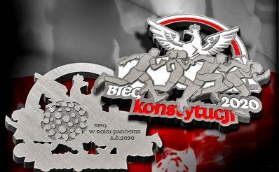 Na zdjęciu przygotowany medal zawodów które odbędą się w Olsztynie 1 maja 2021 r., 1. edycja Olsztyńskiego Biegu Konstytucji 3 maja – Olsztyn 2021. Na medalu wygrawerowane biegnące postacie a nad nimi orzeł.