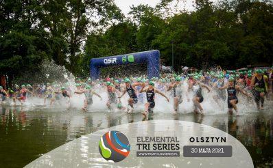 Zdjęcie zapraszające do Olsztyna na zawody Triathlon Elemental Tri Series Olsztyn - 2021. Na zdjęciu widzimy start zawodników nad jeziorem Ukiel, którzy rozpoczynają rywalizację od pływania.