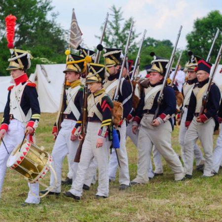 Zdjęcie przedstawia odział wojsk napoleońskich w pełnym rynsztunku maszerujących w stronę obozu. Jest to inscenizacja Bitwy Pod Heilsbergiem (Lidzbark Warmiński), gdzie w roku 1807 starły się wojska rosyjskie  z wojskami Napoleona.
