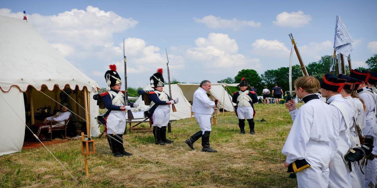 Zdjęcie przedstawia obóz wojsk napoleońskich. Z namiotu wychodzi Napoleon i wita się ze swoimi wojskami. Jest to inscenizacja Bitwy Pod Heilsbergiem (Lidzbark Warmiński), gdzie w roku 1807 starły się wojska rosyjskie z wojskami Napoleona.