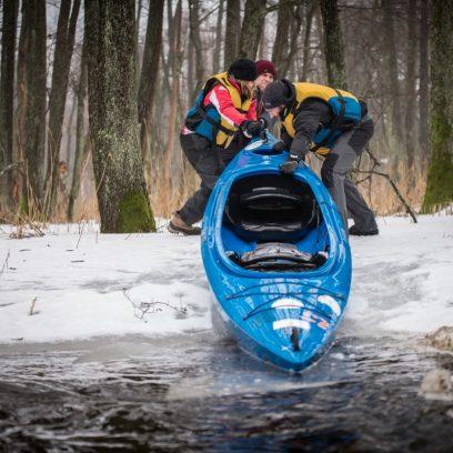 Zimowy spływ rzeką Łaźna Struga. Na zdjęciu trzech kajakarzy wciągających kajak z wody na ośnieżony brzeg leśny.