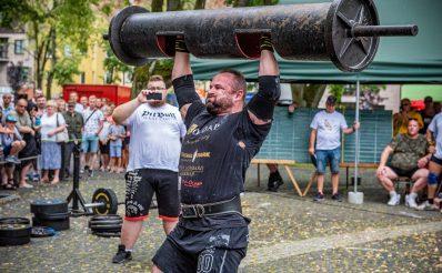 Zdjęcie zapraszające do Gołdapi na 11. edycję Zawodów Strongman Gołdap 2021. Na zdjęciu zawodnik podczas zawodów unoszący nad głową metalową belkę.