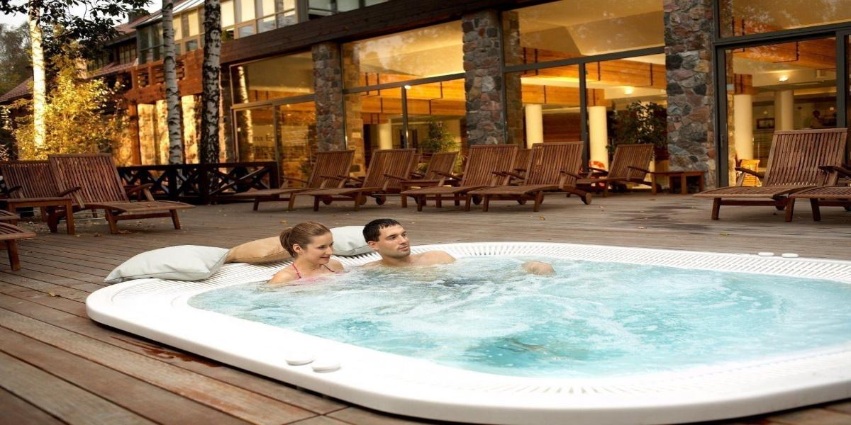 Spa w hotelu Dr. Irena Eris Wzgórza Dylewskie. Na zdjęci jacuzzi na tarasie hotelu, a para gości hotelowych zażywających kąpieli.