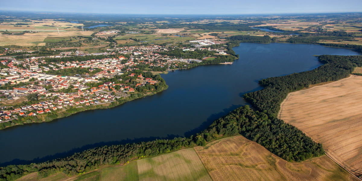 Panorama miasta Olecka. Na zdjęciu widzimy miasto z lotu ptaka oraz jezioro i okalające łąki i pola uprawne.