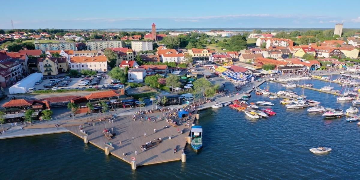 Panorama miasta Mikołajki z lotu ptaka. Na zdjęciu centrum miasta z widoczną przystanią żeglarską.