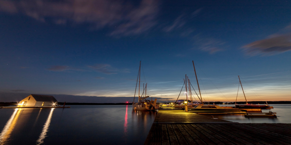 Plaża miejska w Piszu nocą. Na zdjęciu marina w Piszu, przystań żeglarska z zacumowanymi jachtami.