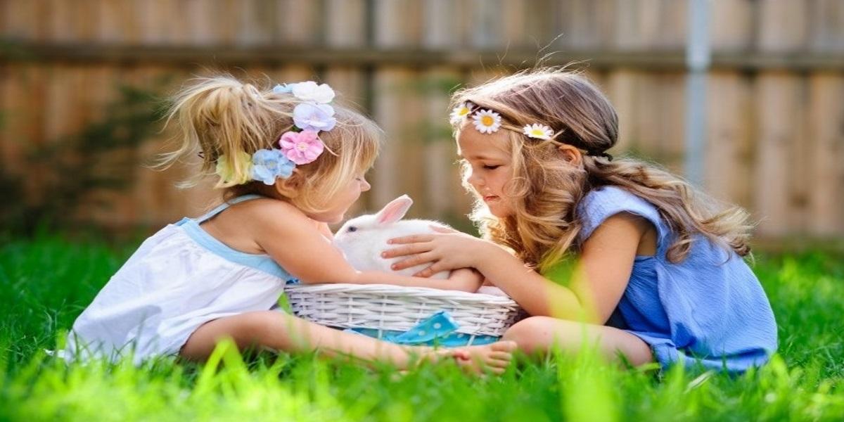 Zdjęcie przedstawia dwie dziewczynki w ogródku, które siedzą przy koszyczku wiklinowym w którym znajnduje się królik.